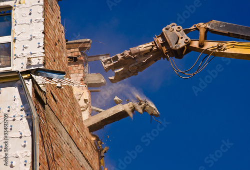 Fotografiet A demolition of a building with a crane with a blue sky background
