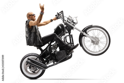 Hardcore biker riding a chopper on one wheel and gesturing rock and roll sign Fototapet