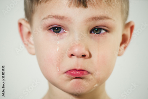 Canvas Print little boy with tears on his face close-up