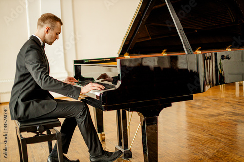 Fotografie, Obraz young handsome caucasian man in formal elegant suit gracefully play piano