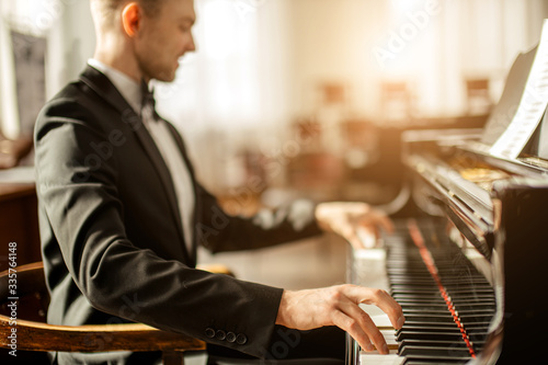 Fotografia gorgeous caucasian male pianist on a stage, man in elegant suit perform classical music for audience
