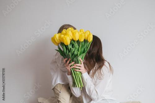 Boy child son congratulates mom with a bouquet of yellow tulips Fototapeta