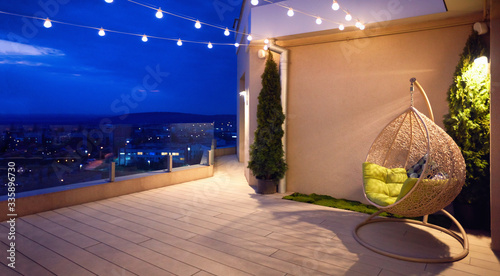 Fotografie, Obraz cozy rooftop terrace with rattan hanging chair, garlands and beautiful landscape