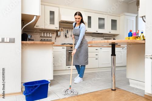 Young woman using mop to clean floor Fototapeta