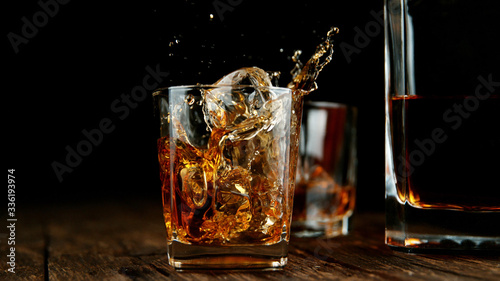 Fotografia Splashing whiskey from glass with ice cubes inside