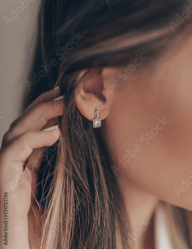Fotografiet Beautiful elegant silver earring with diamond on close-up