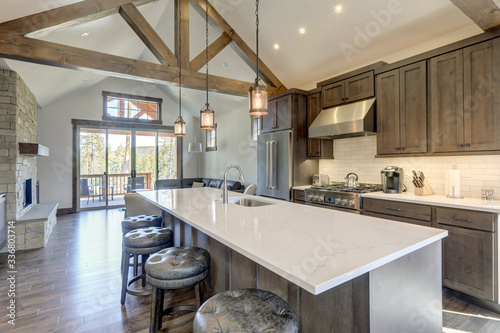 Photo Amazing modern and rustic luxury kitchen with vaulted ceiling and wooden beams, long island with white quarts countertop