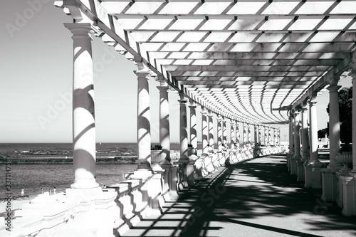 Cuadros en Lienzo Walkway Amidst Colonnades By Sea Against Clear Sky