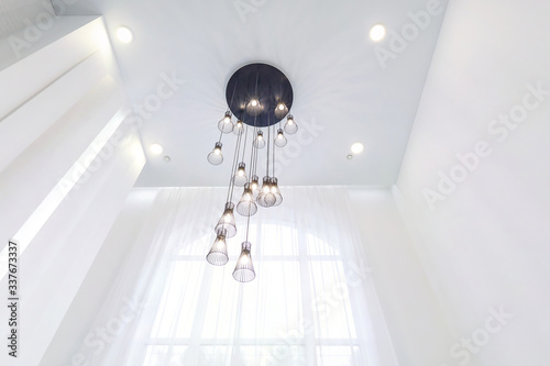 Fotografia looking up on suspended ceiling with halogen spots lamps and drywall construction in empty room in apartment or house