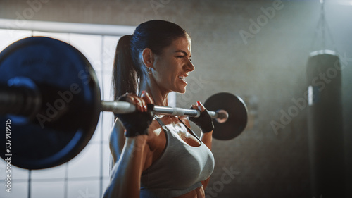 Fotografia Athletic Beautiful Woman Does Overhead Lift with a Barbell in the Gym