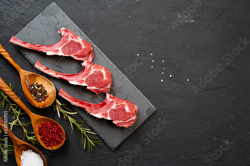 Fotografia Raw fresh lamb ribs on dark background, close up.