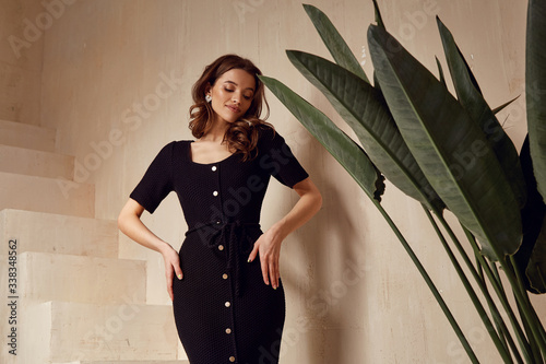 Beautiful woman brunette tanned skin natural makeup wear fashion clothes summer collection black knitted cotton dress on buttons style for summer romantic date interior stairs leaves flowerpot Fototapeta