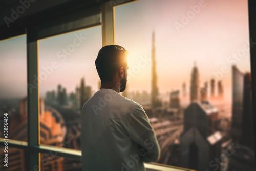 Slika na platnu Arabic business man looking out through the office balcony seen through glass window