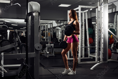 Young beautiful girl athlete bodybuilder does exercises on dark background. Concept - the power of beauty, diet, sports.