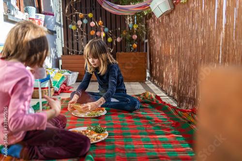 Canvas Print Children enjoying pizza on a balcony picnic