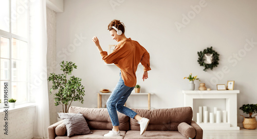 Slika na platnu Cheerful woman listening to music and dancing on soft couch at home in day off
