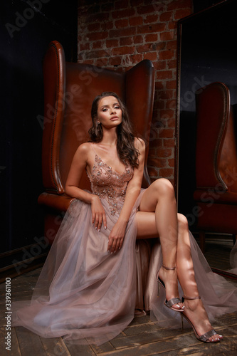 Fotografiet Full length portrait of young beautiful elegant woman sitting and posing at leather chair in dark interior