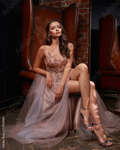 Fotografering Full length portrait of young beautiful elegant woman sitting and posing at leather chair in dark interior