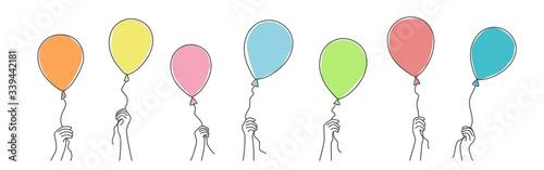 Fotografiet Hands holding balloons. Hand drawn vector illustration