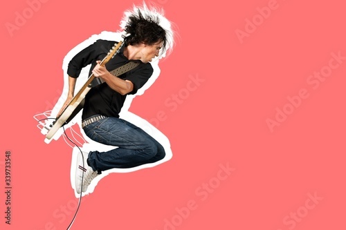 Fotografie, Obraz Male guitarist playing music on guitar and jump