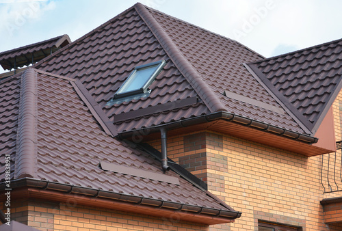 Murais de parede Complex roof design, metal tiled expensive roofing construction with a skylight, snow guards, chimney of a brick house