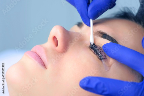 Cosmetologist wiping paint from lashes and brows of woman, side view Fototapeta