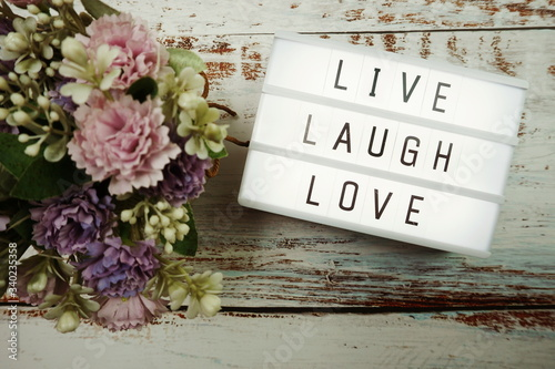 Stampa su Tela Live Laugh Love word in light box flat lay on wooden background