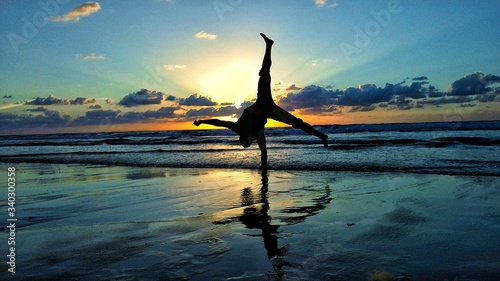 Fotografiet Man Doing Handstand At Beach Against Sky During Sunset