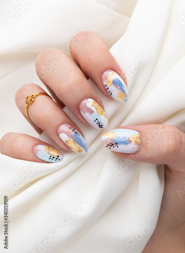 Woman's hand with fashionable nails holding fabric Fototapeta