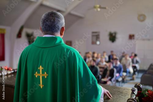 Obraz na płótnie Catholic priest standing on a church podium and preaching, religion