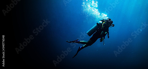 Fotografie, Tablou Woman scuba diving in deep blue sea banner on black background