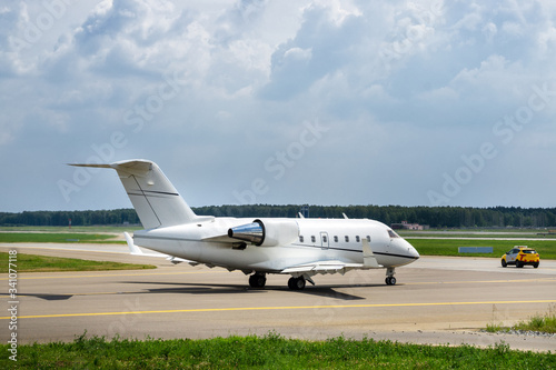 Fotografie, Tablou Airport follow me car guiding the business jet on the taxiway