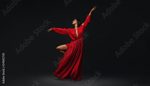 Foto Woman dancing gracefully on black background