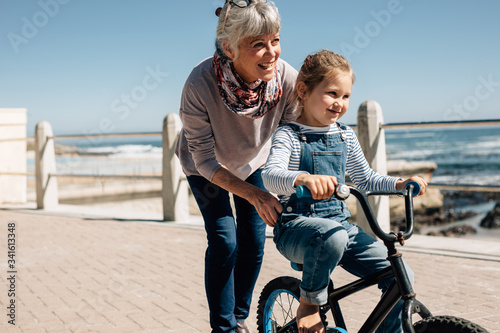 Obraz na plátne Senior woman helping her granddaughter learn to ride a bicycle