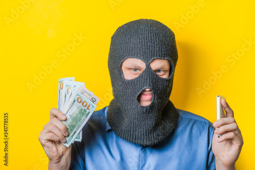 Fotografie, Obraz man close up thief in a mask and a blue shirt on a yellow background looking slyly at the camera, holding the money and the phone