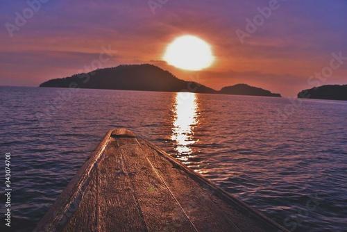 Fototapeta Sampan In Sea Against Sky During Sunset