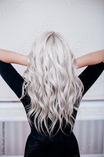 Tela Female back with silver grey ash blonde curly wavy long hair in black dress