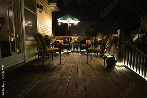 Billede på lærred Furniture At Illuminated Patio During Night