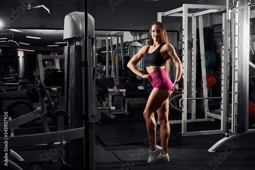 Fitness sexy girl with perfect slim and fit body posing after workout in gym. Sporty woman training and relaxing
