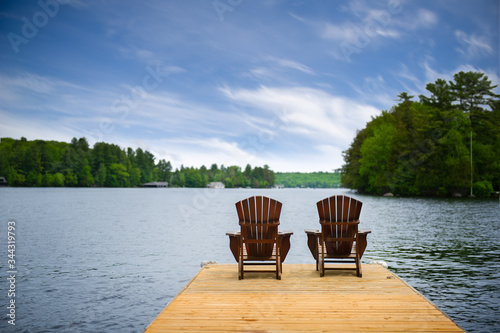 Two Adirondack chairs on a wooden dock overlooking a calm lake Fototapet
