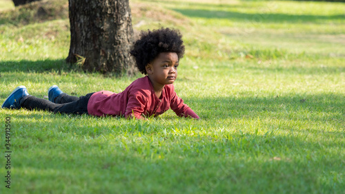 Fényképezés Sad little African boy fell down on the grass and about to cry in the park