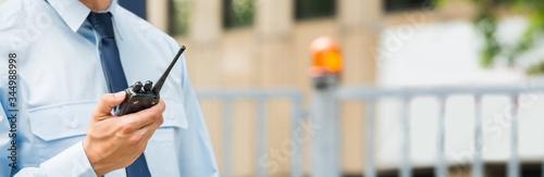 Fotografie, Obraz Security Guard Holding Walkie-talkie