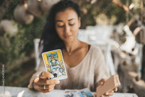 Stampa su Tela Woman is reading Tarot cards sitting at the table outdoors