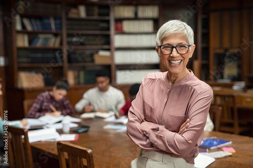 Smiling university professor in library Fototapeta