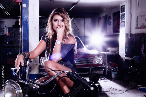 Blonde woman sitting on a black, cool motorcycle in a garage. beautiful blonde woman with long hair in a black mini dress.