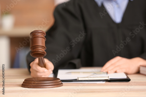 Canvas Print Female judge with gavel at table in office, closeup