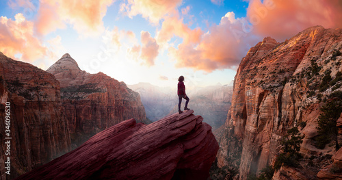 Canvas Print Adventurous Woman at the edge of a cliff is looking at a beautiful landscape view in the Canyon during a vibrant sunset