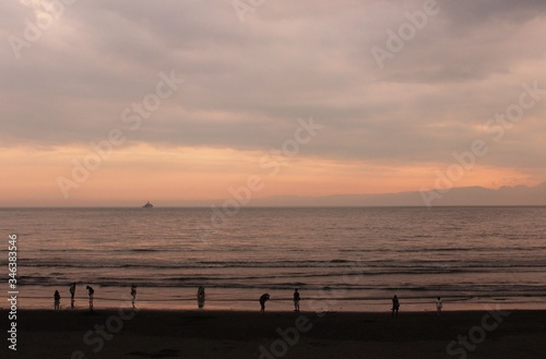 People On Calm Beach At Sunset