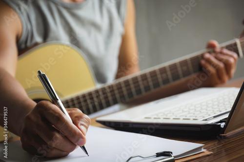 Obraz na plátně Composer holding pencil and writing lyrics in paper