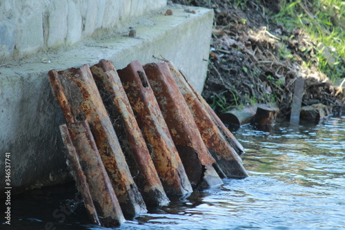 Photo Scrap Metal Leaning On Wall In River